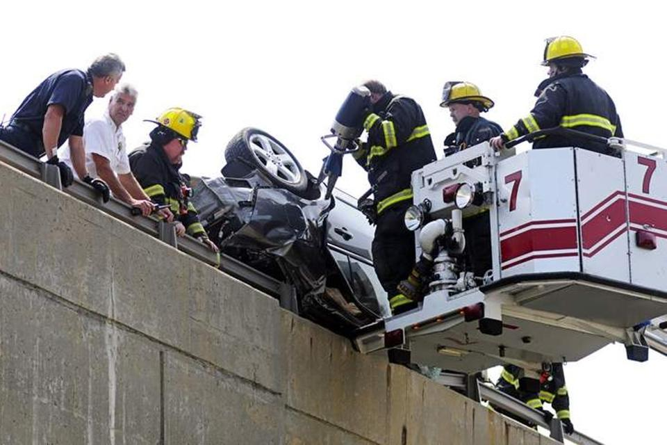 Firefighters use an extrication tool to open a door of the overturned car.