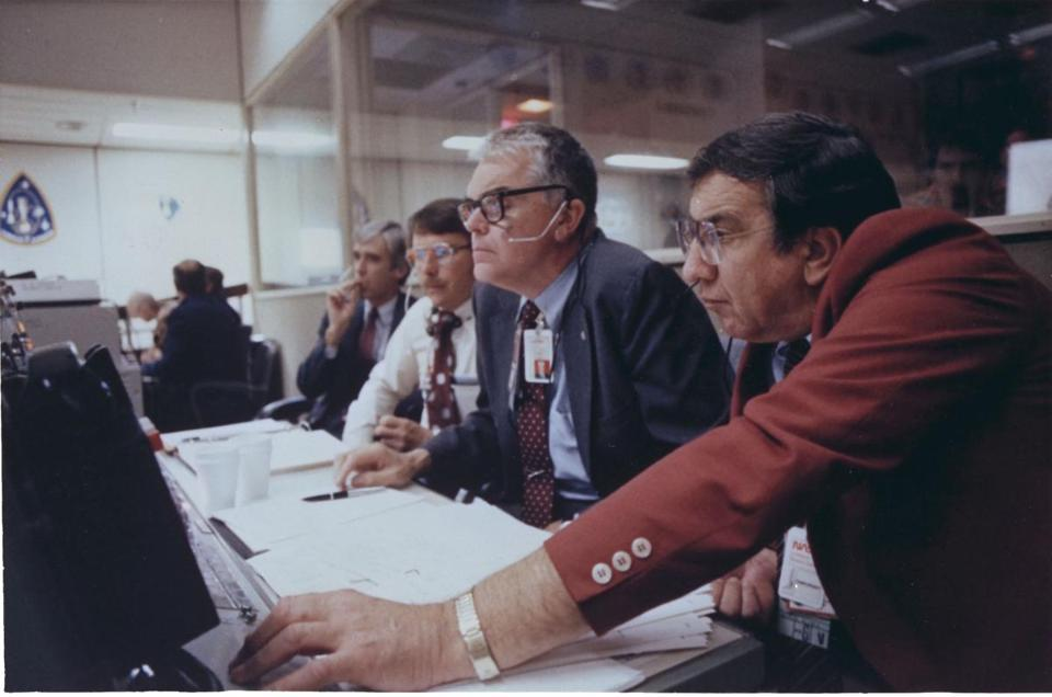 Hans Mark (center), NASA Deputy Administrator, and Milton A. Silveira (right), special assistant to the Deputy Administrator, at NASA's mission control center in 1996.