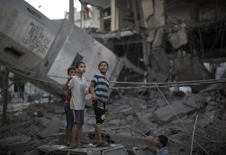"Palestinian youths inspect destruction at a mosque in Gaza City Wednesday after it was hit in an overnight Israeli strike. Israeli bombardments killed ""dozens"" of Palestinians in Gaza, including at least 15 at a UN school, medics said."