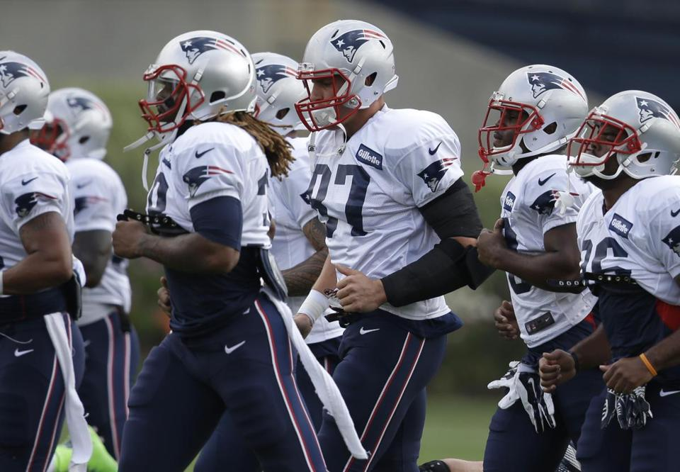 New England Patriots tight end Rob Gronkowski, center, warms up on the field with teammates during an NFL football training camp practice at Gillette Stadium, Sunday, July 27, 2014, in Foxborough, Mass. (AP Photo/Steven Senne)