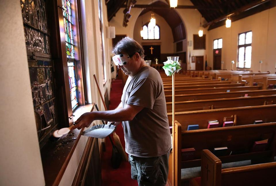 Sexton John Habib cleaned up shards from a broken stained-glass window at the Community United Methodist Church on Thursday.