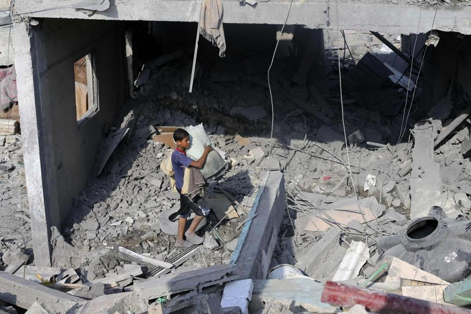 A Palestinian youth carried his belongings from a house in Rafah in the southern Gaza Strip that witnesses said had been hit by an Israeli airstrike.