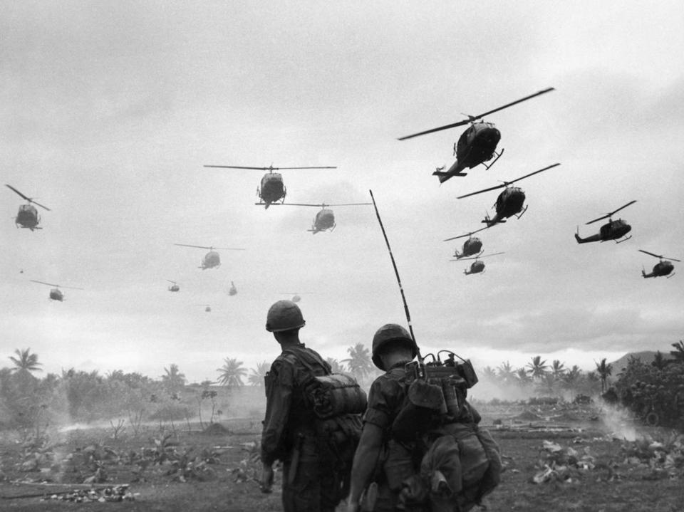 The second wave of combat helicopters of the 1st Air Cavalry Division fly over a radio telephone operator and his commander on an isolated landing zone during Operation Pershing, a search-and-destroy mission on the Bong Son Plain and An Lao Valley of South Vietnam, in January 1967.