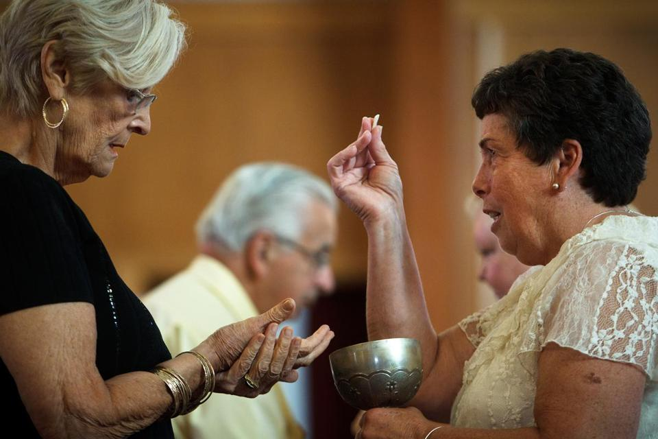 Patty Litz (right) offered communion to Nancy M. Shilts during Mass Sunday at St. Frances X. Cabrini Parish in Scituate. A parishioner group voted unanimously to ask a canonical advocate to argue that the Boston Archdiocese exaggerated its financial woes to justify closing the church in 2004.