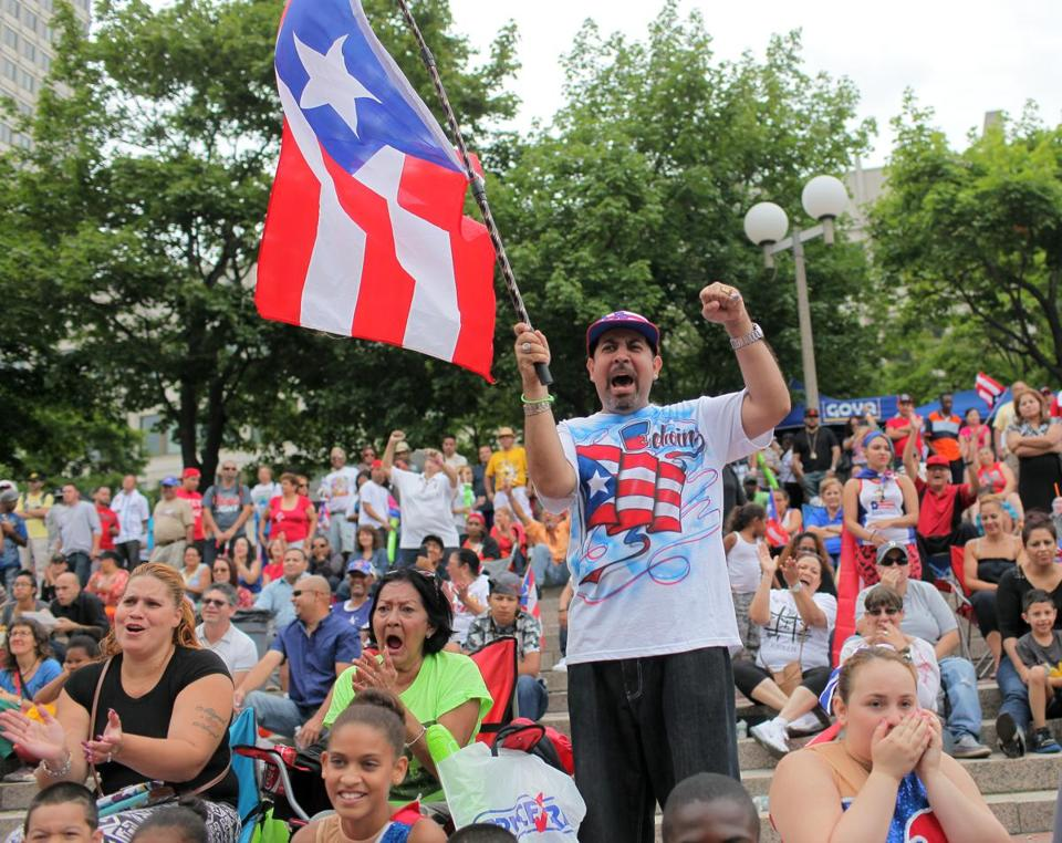 As the crowd in Boston cheered, sang, and clapped, Edwin Reyes demonstrated his pride with a flag and a fist pump during the Puerto Rican Festival parade Sunday.