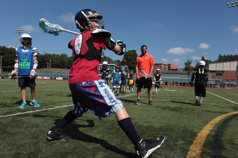 Marcus Ashdown of Wilmington takes a shot during drills. Marcus and other players worked on basic skills in a Prime Time Lax youth camp at North Reading High School. Roughly 1,000 kids have taken part in the camps this summer.