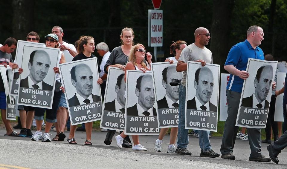 Workers holding signs supporting Arthur T. Demoulas march outside the company's distribution center in Andover.