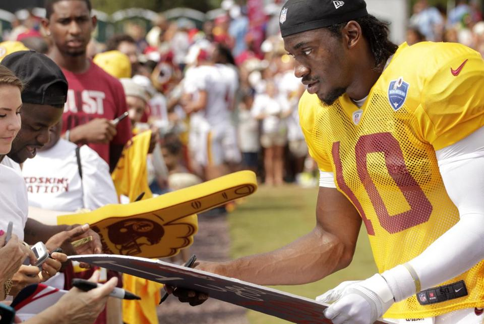 Redskins quarterback Robert Griffin III signed autographs after practice with the Patriots Monday.