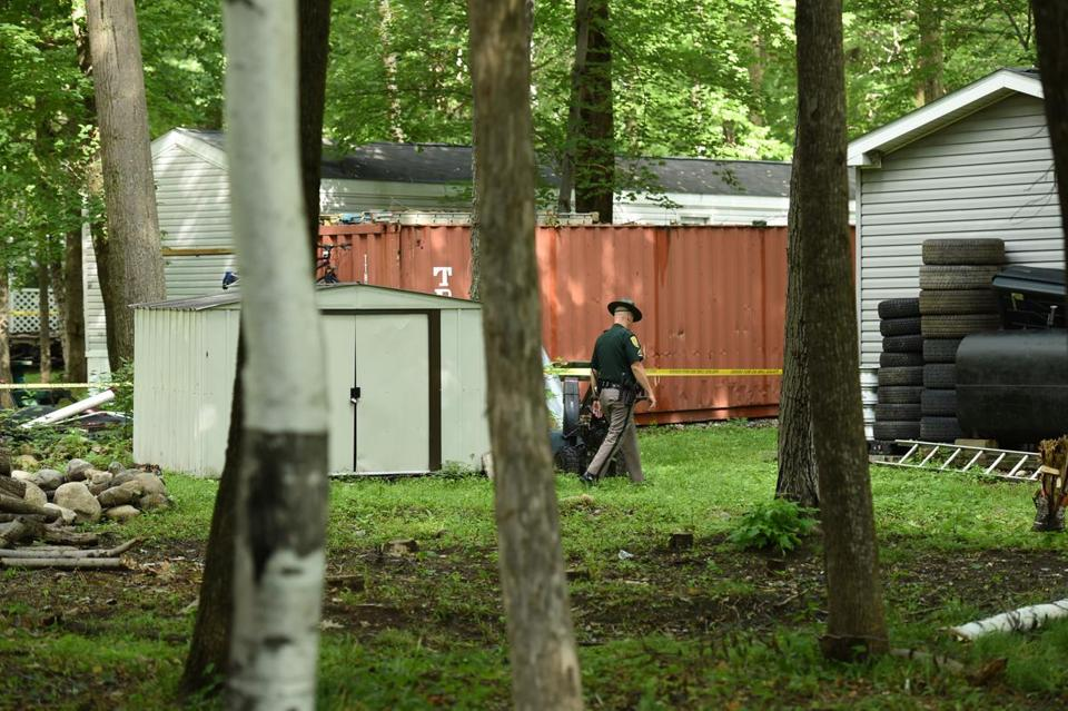 A New Hampshire State Trooper walked near a cargo container on the property of Nathaniel Kibby.