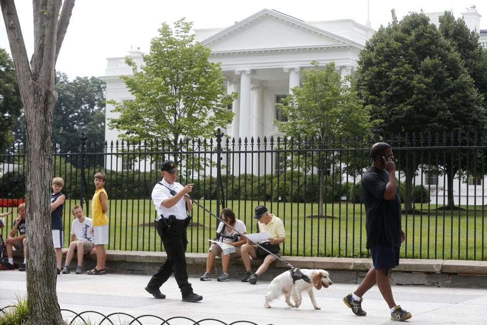 A Uniformed Division Secret Service police officer patrols in front of the White House in July. A toddler squeezed through the fence at 1600 Pennsylvania Ave. Thursday.