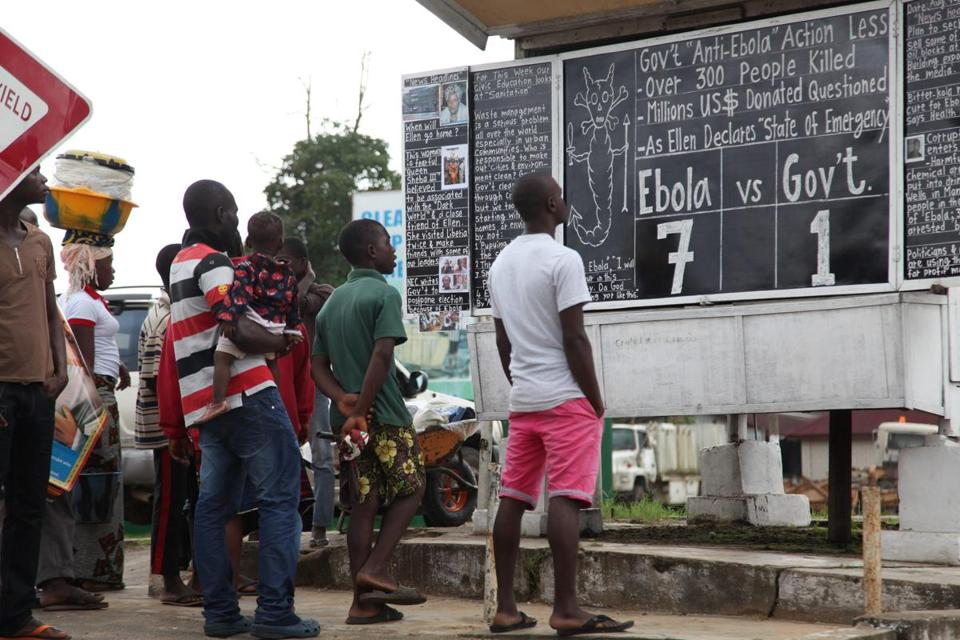 Liberians read a chalkboard on the Ebola outbreak in Monrovia on Saturday. Guinea closed its borders with Sierra Leone and Liberia to try to curb the virus.