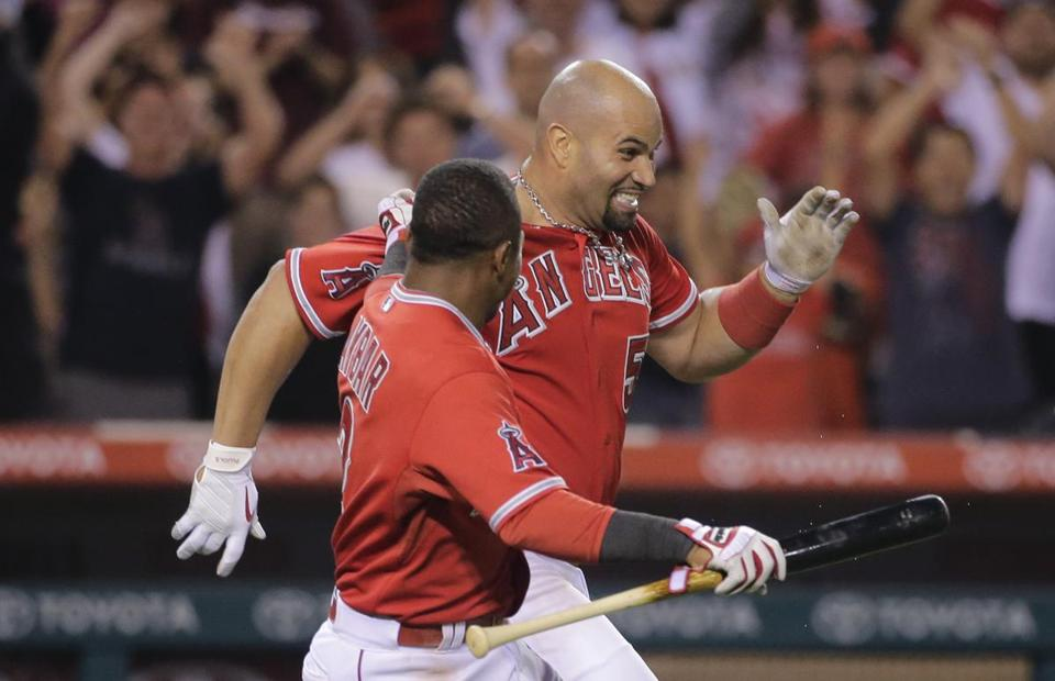 Angels infielder Albert Pujols (right) celebrated with teammate Erick Aybar after Pujols' game-winning home run in the 19th inning.