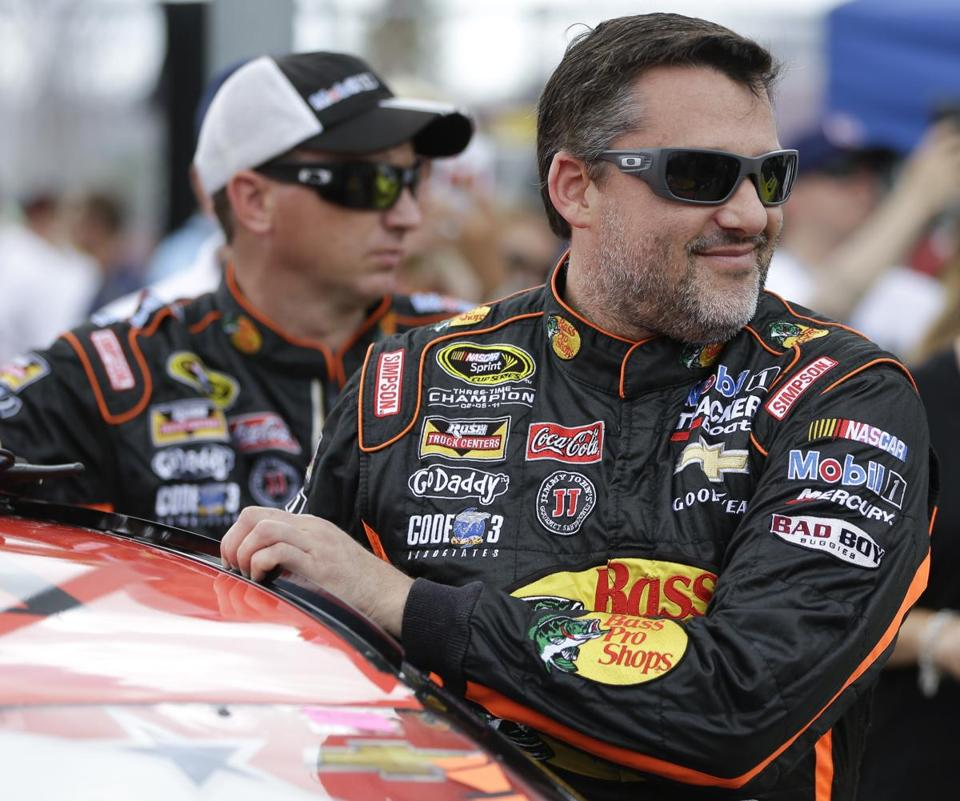 Tony Stewart stands by his car before the start of the NASCAR Sprint cup Series auto race in Daytona Beach, Fla., last month.