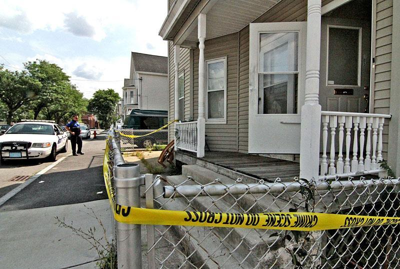 Police tape was outside the house at 105 Andrews St. in Lowell were the brothers were found.