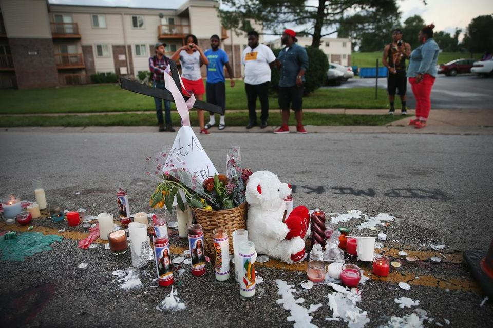 People view a memorial in the street where 18-year-old Michael Brown was shot by police.