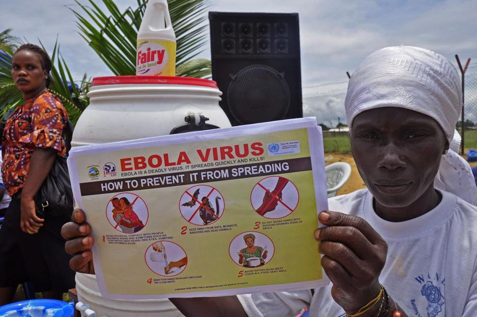 A Liberian woman holds up a pamphlet with guidance on how to prevent the Ebola virus from spreading.