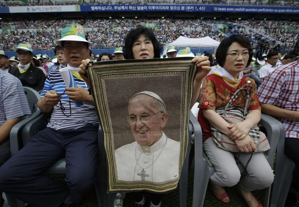 A woman held a picture of Pope Francis as the crowd waited for his arrival to attend a Mass on Friday.