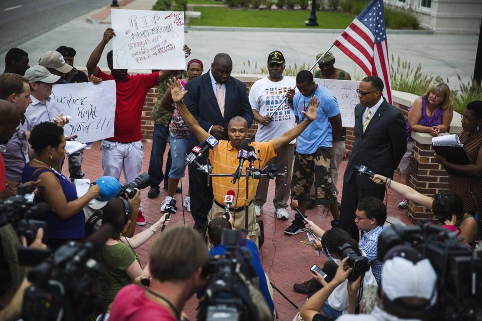 Eric Davis, Michael Brown's cousin, dropped to his knees and raised his hands as he spoke to the media about Saturday's fatal police shooting and the authorities' response to ensuing protests.