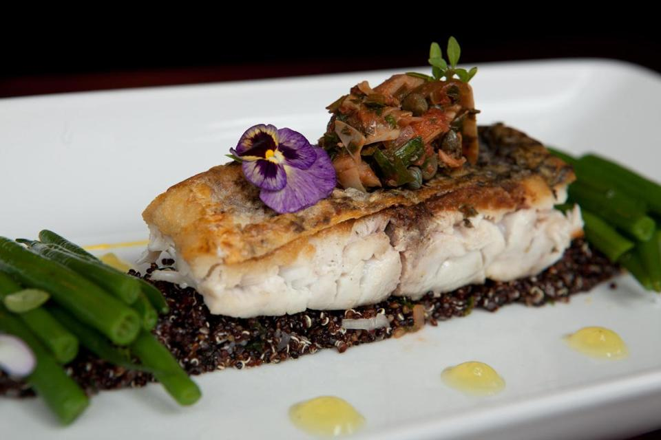 "Boston, MA - 08/15/14: Local Striped Bass is served at Parla restaurant in Boston, Massachusetts. The dish consists of local striped bass on a bed of black quinoa salad, artichoke heart relish, citrus ""pudding"", sautŽed green beans, and saffron aioli. (Kayana Szymczak for the Boston Globe)"