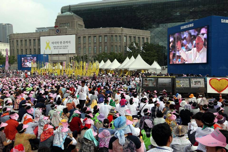 Pope Francis was displayed on a screen as a crowd gathered in Seoul Plaza to watch the beatification ceremony.