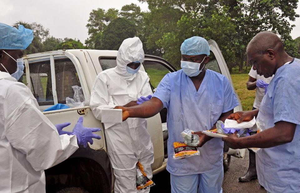 Health workers were handed protective gear before collecting bodies of Ebola victims from streets in Monrovia, Liberia.