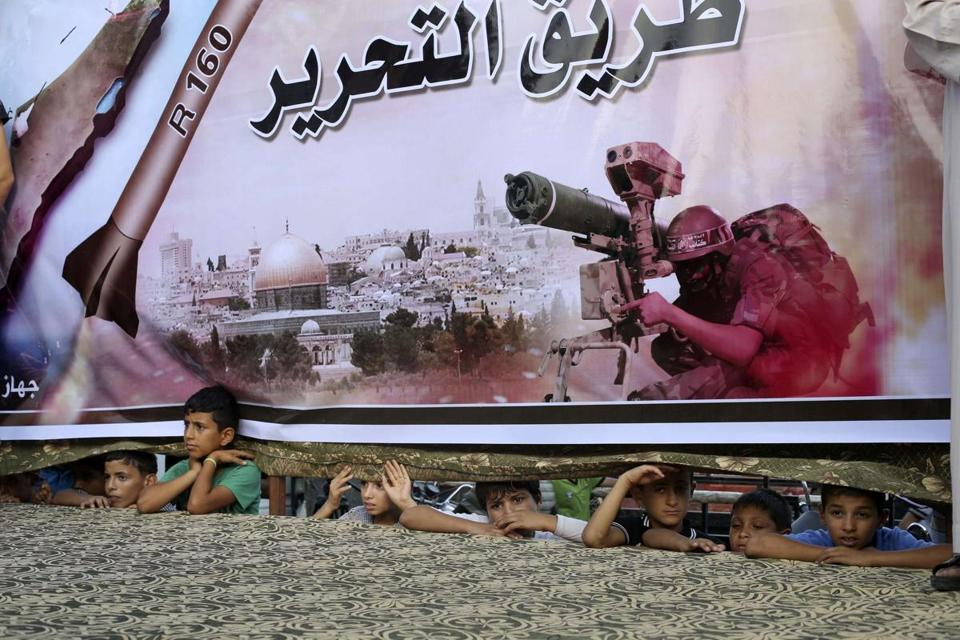 Gaza residents watched beneath a Hamas poster at a rally in support of the armed Palestinian factions Sunday.
