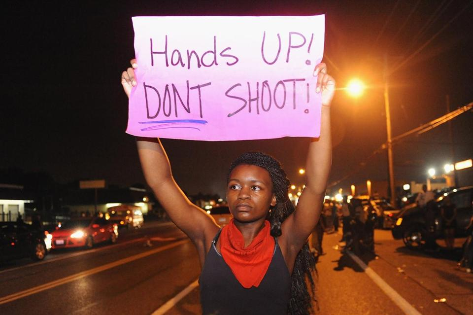 Protestors held signs during a protest on West Florissant Road in Ferguson.