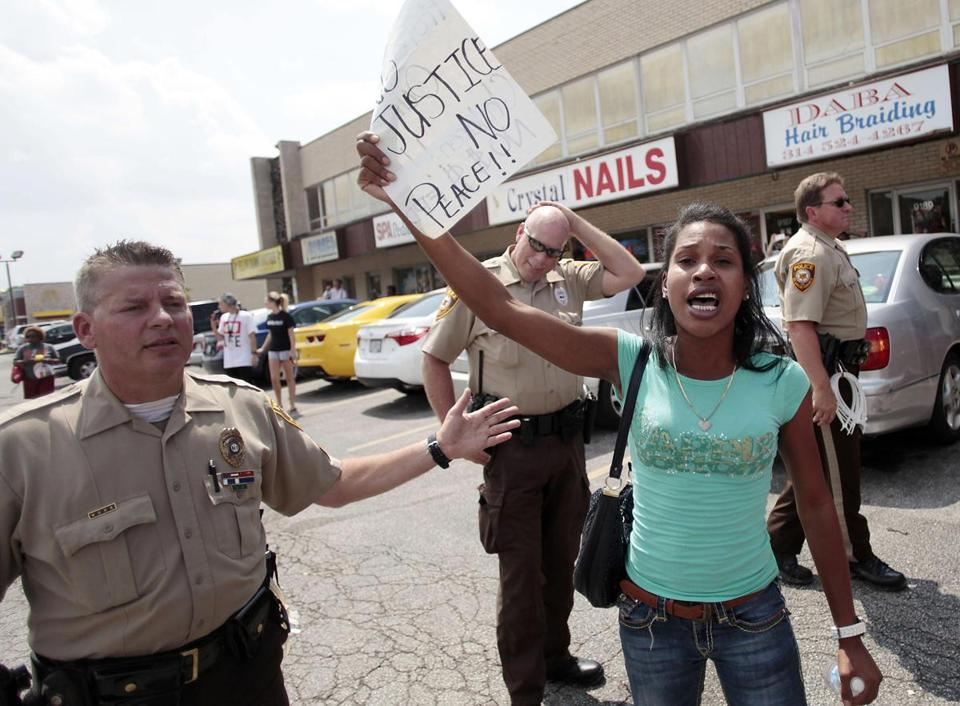 Officers and a protester were in Ferguson, Mo., Monday.