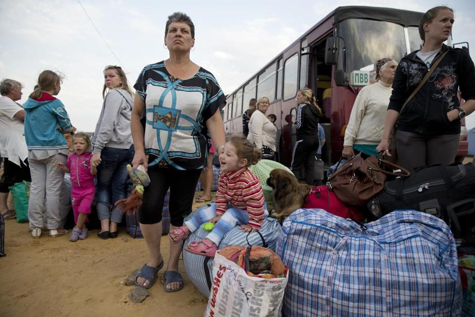 Refugees in Ukraine waited to board a bus on Monday before traveling to a camp in the Russian Siberian city of Irkutsk, where they are being relocated.