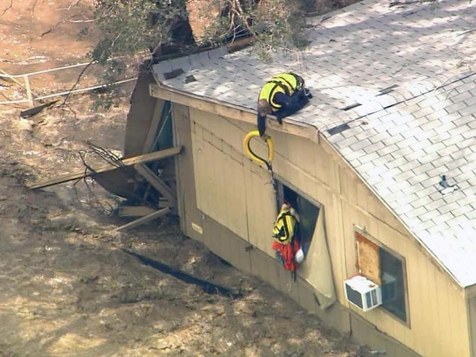 A rescue worker from a helicopter reached down to residents of a flooded house in New River, Ariz., north of Phoenix.