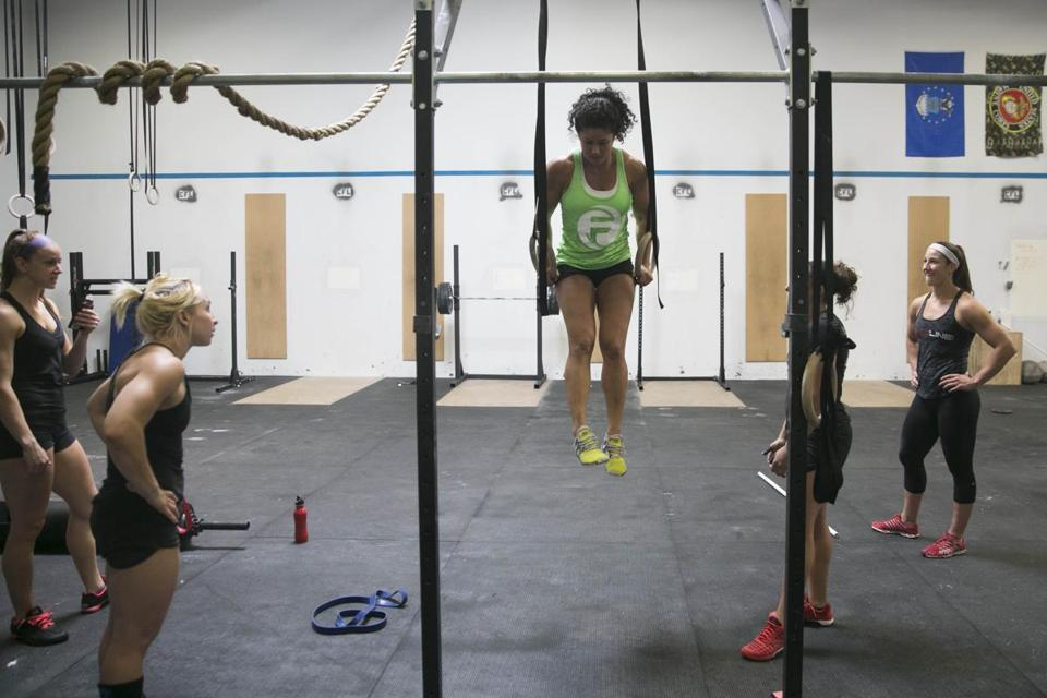 Jessa Lemoine practiced on the rings as her Boston Iron teammates watched at CrossFit Lando in Woburn. Teams feature five men and five women. In one extra twist, at least one man and one woman must be 40 or older.