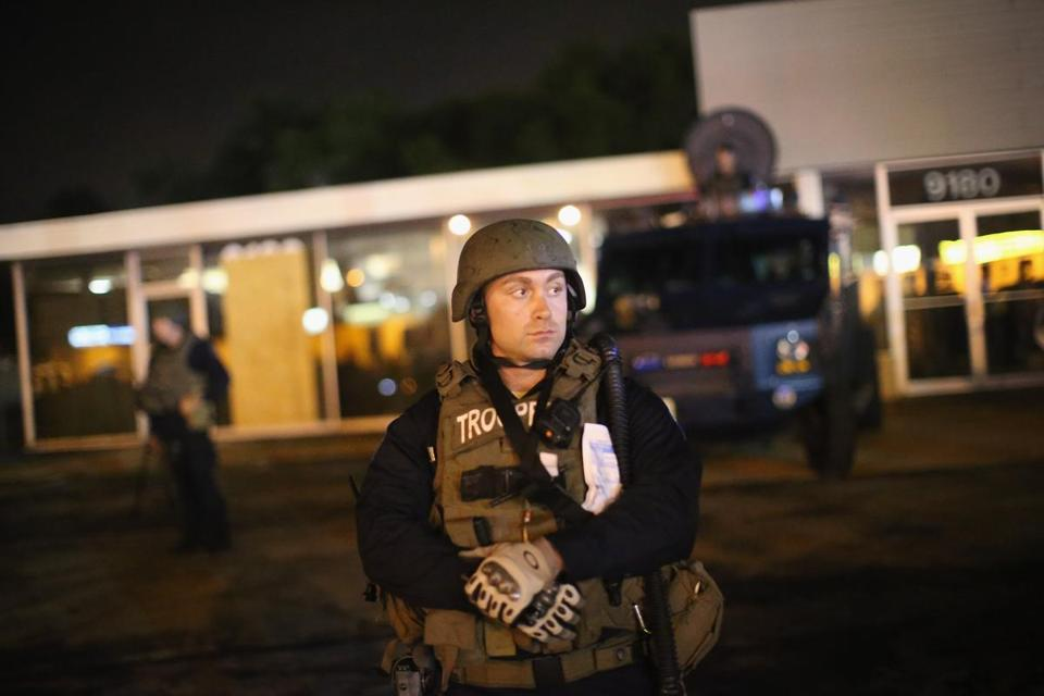 Police watched as demonstrators protested Wednesday in Ferguson, Mo.