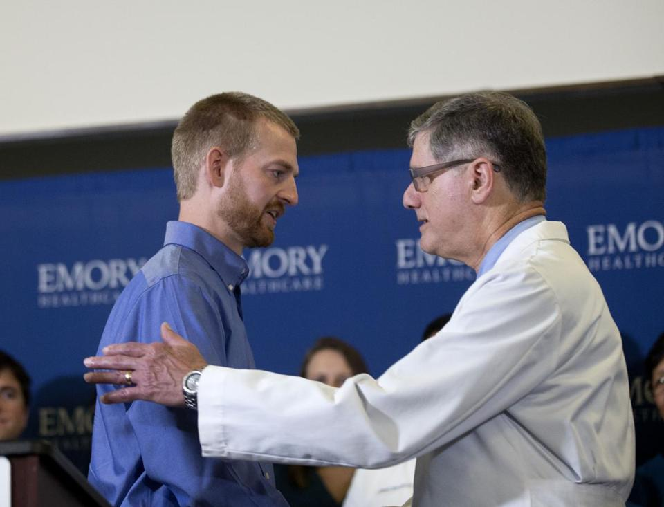 Ebola victim Dr. Kent Brantly, left, embraces Dr. Bruce Ribner, medical director of Emory's Infectious Disease Unit, after being released from Emory University Hospital on Thursday.