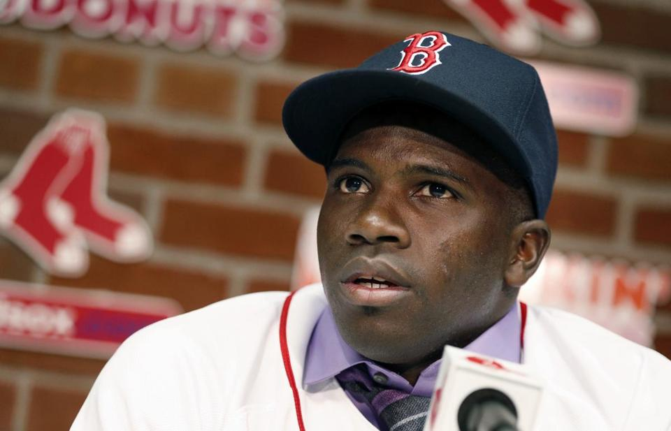 Outfielder Rusney Castillo talks with reporters following his official signing with the Red Sox to a seven-year contract Saturday. (Michael Dwyer/Associated Press)
