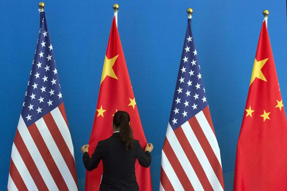 A woman adjusts a flag during the US-China Strategic and Economic Dialogue in Beijing in July.