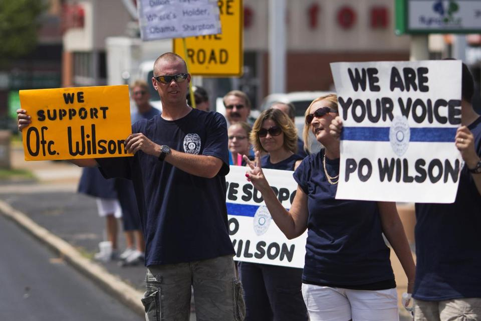 Supporters of Officer Darren Wilson held placards outside a St. Louis pub during a rally Saturday.