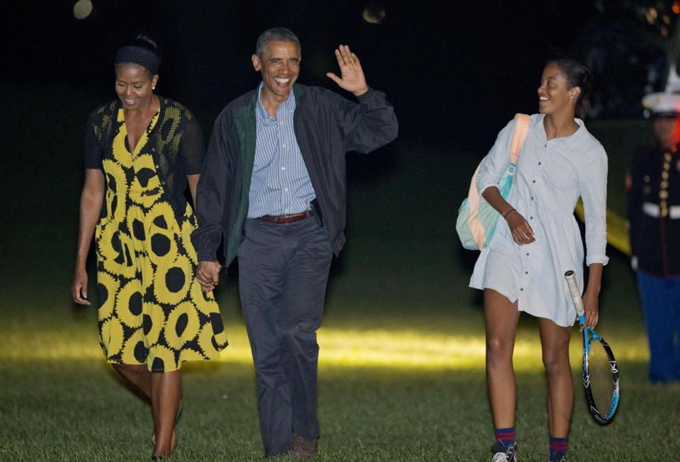 President Obama and first lady Michelle Obama (left) walk with their daughter Malia across the South Lawn of the White House on Sunday night.
