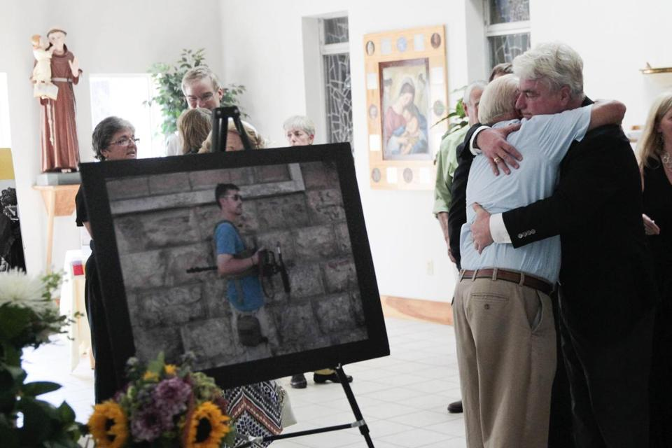 John Foley (right), father of James Foley, hugged a man during a memorial service for the slain journalist at the Our Lady of the Holy Rosary Church in Rochester, New Hampshire.
