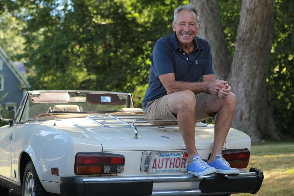 Playwright and filmmaker Israel Horovitz sits on the back of his car showing his vanity plate.