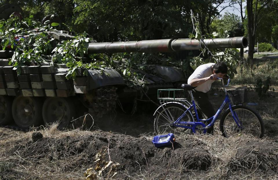 A resident of Novoazovsk, Ukraine, walked his bike passed a pro-Russia tank.  At least a half dozen tanks used by rebel fighters were seen on roads around town.