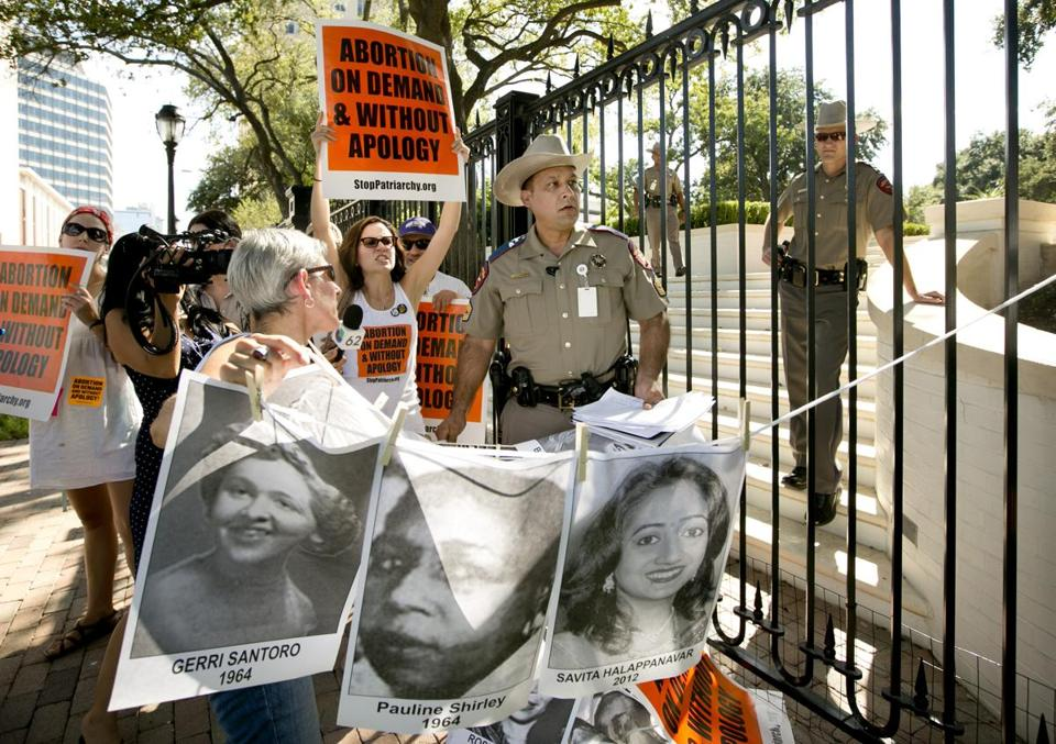Pro-abortion rights activists chanted slogans on Monday while a Texas Department of Public Safety trooper removed their signs from the gate of the Governor's Mansion in Austin.