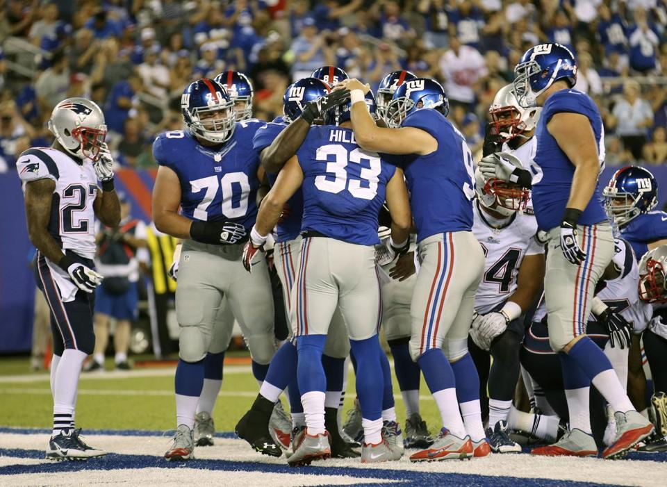 The Giants congratulated Peyton Hillis after he scored a touchdown against the Patriots.