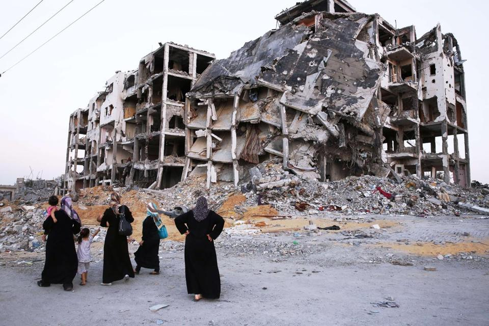 Palestinians looked at the remains of a building that was destroyed in recent fighting in Gaza.