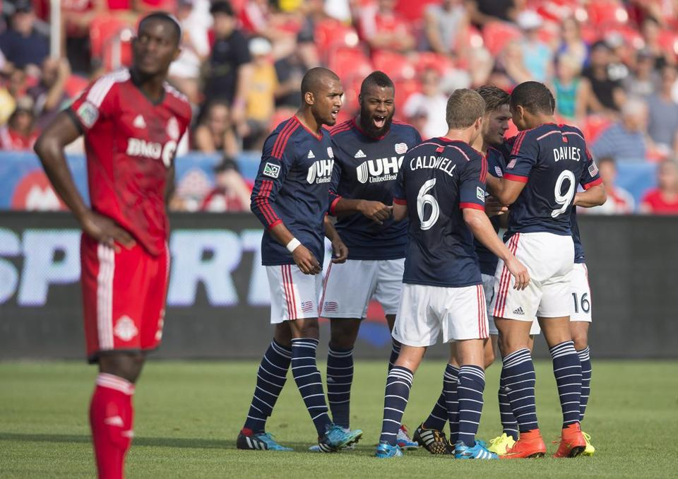 Doneil Henry averts his eyes as Revolution players celebrate a first-half goal Saturday at BMO Field in Toronto.