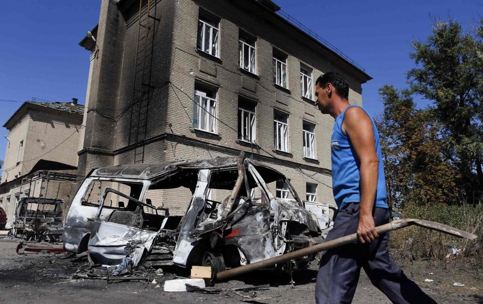 A man on Sunday walked past vehicles destroyed in recent shelling in the eastern Ukrainian town of Ilovaysk.