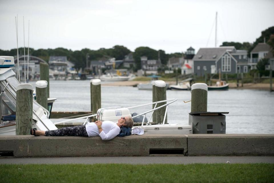 Laura Smales of Toronto relaxed along the wall overlooking Hyannis Harbor on Sunday.