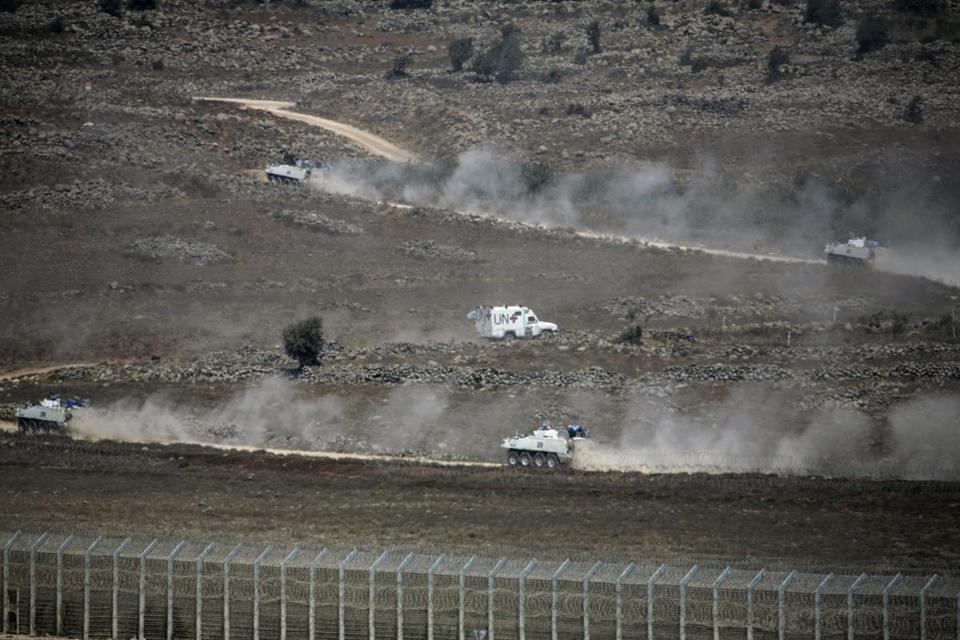 UN vehicles drove in Syria near a fence bordering the Israeli-occupied Golan Heights Sunday. The head of the Fijian army said negotiations for the release of 44 soldiers seized on the Syrian side by an Al Qaeda-linked group were being pursued.