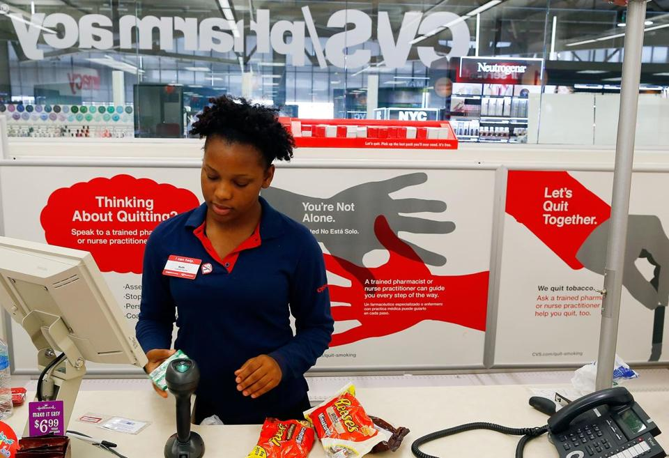 Cashier Ruth Jean, 19, rings up a sale at a CVS in Boston in front of signs that deliver the company's antismoking message. Jessica Rinaldi/Globe Staff