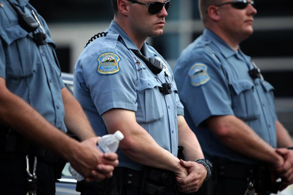 Police officers wore what appeared to be body cameras as they held the line against protesters gathered at the police station during a rally in Ferguson, Mo., last month.