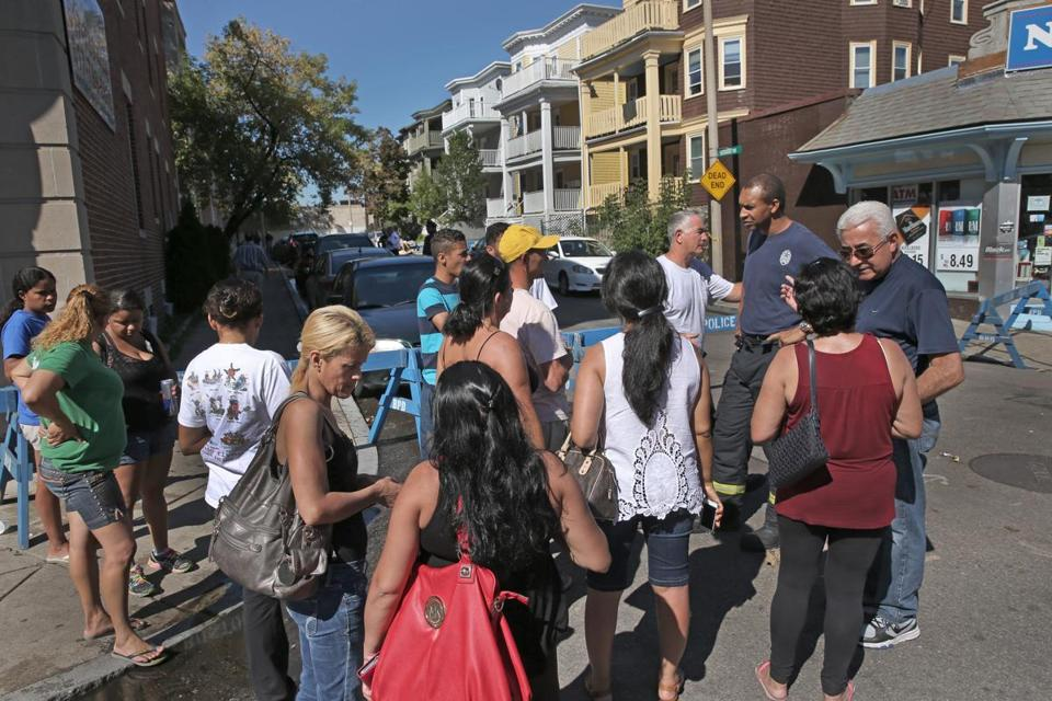 Residents and Boston fire officials stand Thursday at the end of Harvard Terrace in Allston, where Wednesday's 9-alarm fire caused a roof to collapse.